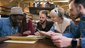 Företag av lyckliga vänner som diskuterar disk från menyn för beställning i stången, bar stock video