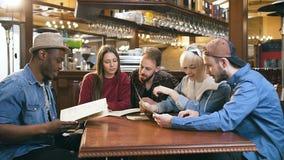 Företag av unga vänner som läser menyn och väljer disk för beställning i stången, bar arkivfilmer