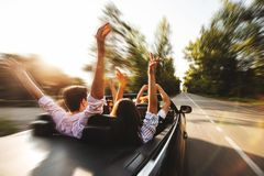 Företag av ungdomarsom rider i en cabriolet på vägen och ho royaltyfri foto