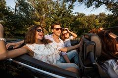 Företag av ungdomarsom rider i en cabriolet på vägen på en varm solig dag Två härliga flickor och en ung man arkivfoton