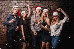 Företag av vänner, i att dansa för jultomtenlock royaltyfri foto