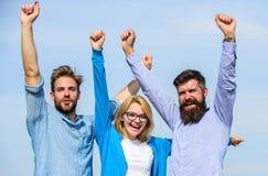 Företag nådd överkant Män med skägget i formell skjortor och blondin i glasögon som det lyckade laget Företag av lyckliga tre royaltyfri fotografi