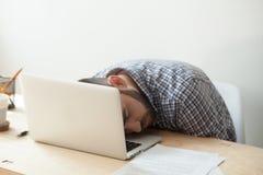 Företags anställd som sover på hans bärbar datortangentbord efter deadlin arkivfoto