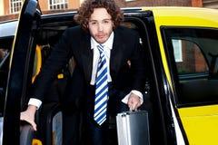 Företags grabb som får ut ur en taxitaxi Arkivfoto