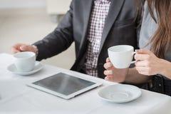 Företags kaffeavbrott! Unga businesspeople som sitter på tablen Arkivbild