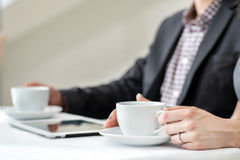 Företags kaffeavbrott! Unga businesspeople som sitter på tablen Arkivfoton