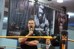 Företags Kane talar in i mic med armar som korsas i cirkel Royaltyfri Fotografi