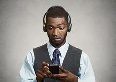 Företags ledare med hörlurar som rymmer mobiltelefonen royaltyfri bild
