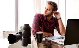 Företagsam fotograf som ser av kamera på hans skrivbord Arkivbilder