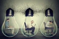 Företagsanställda som sitter i kula för elektrisk lampa för radinsida ljus genom att använda bärbara datorn Royaltyfri Fotografi