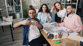 Företagsanställda som tar selfie i idérikt kontor genom att använda smartphonekameran arkivfilmer