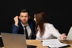 Företagsexecutiv som arbeta som privatlärare åt den unga personliga sekreterareassistenten royaltyfria foton