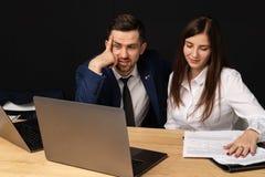 Företagsexecutiv som arbeta som privatlärare åt den unga personliga sekreterareassistenten arkivbild