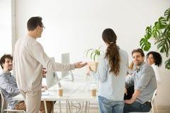Företagsframstickande som introducerar ny hyraanställd till kollegor, bakre v arkivbild