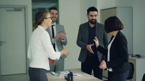 Företagsvd:n gratulerar en lyckad kandidat efter jobbintervjun som skakar hennes hand, och le, är folket arkivfilmer