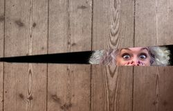 Förfärad kvinna som kikar till och med ett mellanrum arkivfoton