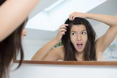 Förfärad ung kvinna som ser i spegeln royaltyfria foton