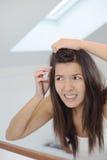Förfärad ung kvinna som ser i spegeln royaltyfri fotografi