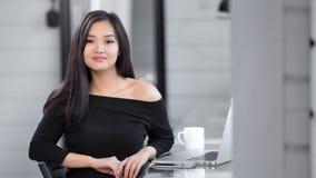 Förförisk asiatisk modeflicka för stående som bär svart klänningsammanträde på arbetetabellen stock video