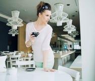 Förförisk brunettflicka som rymmer en kopp kaffe Arkivbilder