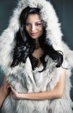 Förförisk brunettkvinna som bär det stilfulla pälslaget arkivbild