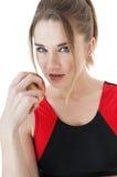 Förförisk idrotts- flicka i träningsoverall som äter ett rött äpple. Arkivfoto