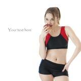 Förförisk idrotts- flicka i träningsoverall som äter ett rött äpple. Arkivbild