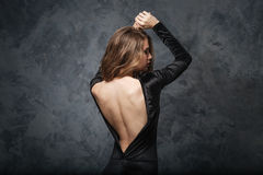 Förförisk ung kvinna i aftonklänning med öppet tillbaka arkivbild