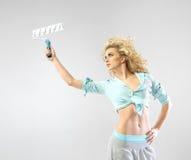 Förförisk ung kvinna som rymmer målarfärgrullen Fotografering för Bildbyråer