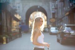 Förförisk ung modell med långt hår som rymmer exponeringsglas som poserar på passagen i strålar av solen kopiera avstånd fotografering för bildbyråer