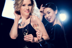 Förföriska multietniska flickor som rostar med champagneexponeringsglas och har gyckel på partiet Arkivfoto