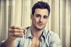 Förföriskt stiligt dricka för sammanträde för ung man royaltyfri bild