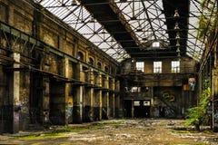 Förfalla industribyggnad inom sikt arkivfoto