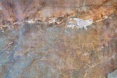 Förfallen betongvägg med sprickor och skrapor, textural lodisar Arkivfoto