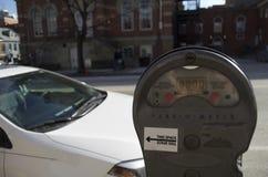 Förfallen parkeringsmeter med den parkerade bilen Arkivfoton
