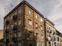 Förfallen sliten klassisk hyreshusfasad i stadsstree Arkivfoto