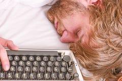 Författare använd gammalmodig skrivmaskin Författaren rufsade till hår faller sovande, medan skriv boken Arbetsnarkomanen faller  royaltyfri fotografi