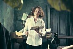Författare på arbete Stiligt ungt författareanseende nära tabellen och utgöra något i hans mening royaltyfria foton