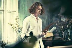 Författare på arbete Stiligt ungt författareanseende nära tabellen och utgöra något i hans mening royaltyfri foto