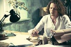 Författare på arbete Stiligt ungt författaresammanträde på tabellen och handstilen något i hans sketchpad royaltyfria foton