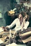 Författare på arbete Stiligt ungt författaresammanträde på tabellen och handstilen något i hans sketchpad royaltyfri fotografi