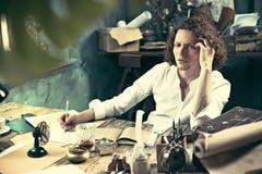 Författare på arbete Stiligt ungt författaresammanträde på tabellen och handstilen något i hans sketchpad royaltyfri bild
