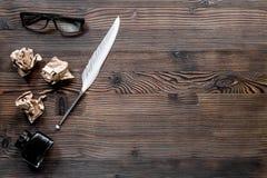 Författarebegrepp Befjädra pennan, ink och skrynklade papper på träcopyspace för bästa sikt för tabellbakgrund Arkivfoto