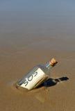 Förfrågan för hjälp i en flaska på stranden Arkivbild