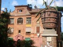 Förgrund av en vas av den graved dekorerade bilskrället med trots allt en forntida byggnad av det populära området Garbatella i R Royaltyfria Bilder