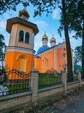 Förgylla av kyrkliga kupoler med kors på taket av det kyrkliga anseendet bak ett lågt staket med ett krökt staket Arkivfoton