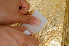 Förgylla det guld- arket på stålboll och Buddhastatyn Arkivbild