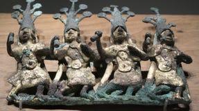 Förgylld bronsbucklaprydnad med fyra dansare Arkivbilder