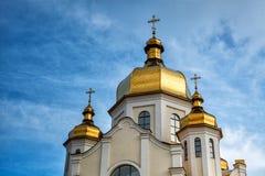 Förgyllda kupoler av den ortodoxa kristna kyrkan skiner på den blåa himlen Arkivbilder