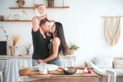 Förhållande i familjen med småbarn Farsan och mamman kysser i det ljusa köket, barn hjälper att laga mat i köket arkivfoton